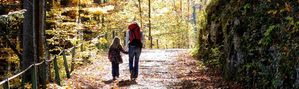 image of mother and daughter walking along a park trail